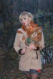 Spätherbst im Wald, Waldsee, blondes Mantelmädchen durch den See Stockfoto