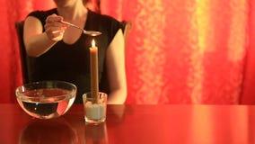 Spådom med stearinljuset hällande vax för kvinna in i vattnet lager videofilmer