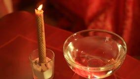 Spådom med stearinljuset hällande vax för kvinna in i vattnet arkivfilmer