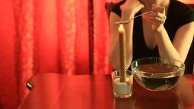 Spådom med stearinljuset hällande vax för kvinna in i vattnet stock video