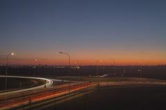 Spårämnar för nattsiktsgata med magisk solnedgång i den Lettland Daugavpils staden Fotografering för Bildbyråer