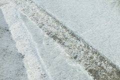 Spår av bilen på is Textur av isyttersida Arkivbild