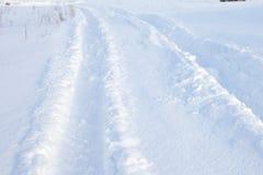 Spår för bilgummihjul i ny snö arkivfoto