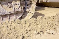 Spår för crawlsimmare` s, bulldozermaskin jämnar konstruktionsplatsen arkivbild