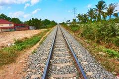 Spår för järnvägdrev går till horisonten med palmträd royaltyfri foto