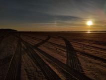 Spår för solnedgångstrandgummihjul arkivbilder