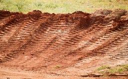 Spår från bilen på jorden för röd lera Fotografering för Bildbyråer