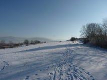Spår på insnöat bergen Den härliga vintern landscape Royaltyfri Bild