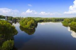 Spåra en bred flod med höga gröna träd på bankerna mot bakgrunden av den blåa himlen royaltyfria foton