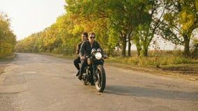 Spåra skottet av den stiliga mannen i solglasögon som rider en motorcykel med hans flickvän bakom som tillsammans reser på stock video
