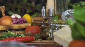 Spåra upp skjutit slut för matsammansättning Matbakgrund från grönsaken, oliv, örter, ost, smaktillsats på trä lager videofilmer