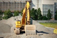 Spårad grävskopa på en konstruktionsplats bland högar av den krossade stenen Royaltyfri Bild