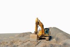 Spårad grävskopa på en konstruktionsplats bland isolerade högar av spillror royaltyfria bilder
