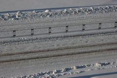 Spårar av bilar på snön på vägen, körbanan, vägsäkerhet is för dubbade gummihjul Den soliga dagen vår är nära arkivfoto