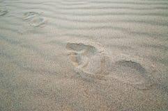 Spårar av kvinnlig kal fot på ren sand arkivfoto