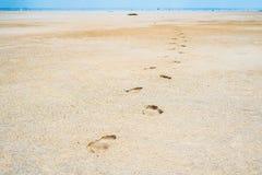 Spårar av mänskliga ben som sträcker in i sanden på det kust-, blir grund av den salta sjön Baskunchak arkivfoton