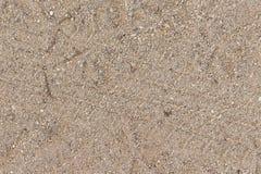 Spårar i sanden texturerad bakgrund Arkivfoto