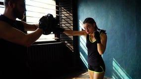 Spåring av skottet av vit kvinnlig boxareutbildning för passform med boxninglagledaren på idrottshallen lager videofilmer