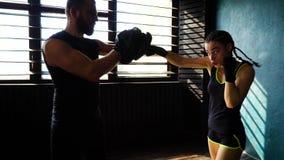 Spåring av skottet av vit kvinnlig boxareutbildning för passform med boxninglagledaren på idrottshallen arkivfilmer