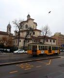 Spårvagn och kyrka för tappning gul bak den på gatan av Milan, Italien royaltyfri fotografi