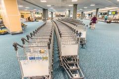 Spårvagnar för bagage av passagerare i flygplatsbyggnaden arkivbild