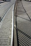 Spårvagnlinjer, trottoar, räcke, metalliskt skyddsstaket och skuggor royaltyfria bilder