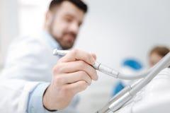 Spécialiste ambitieux déterminé voulant utilisant un foret dentaire Photo libre de droits