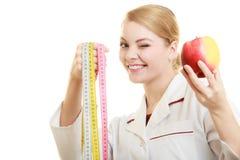 Spécialiste en docteur tenant la pomme de fruit et la bande de mesure Photos stock