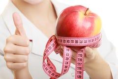 Spécialiste en docteur tenant la pomme de fruit et la bande de mesure Photographie stock