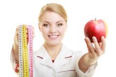 Spécialiste en docteur tenant la pomme de fruit et la bande de mesure Images libres de droits