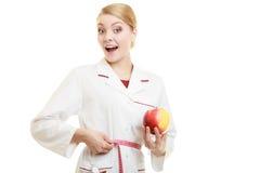 Spécialiste en docteur tenant la taille de mesure de pomme de fruit Images stock