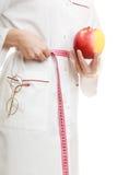 Spécialiste en docteur tenant la taille de mesure de pomme de fruit Photographie stock libre de droits