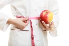 Spécialiste en docteur tenant la taille de mesure de pomme de fruit Photo libre de droits