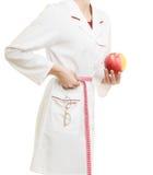 Spécialiste en docteur tenant la taille de mesure de pomme de fruit Photos libres de droits