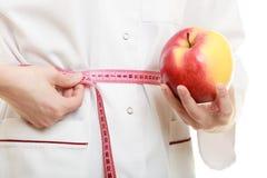 Spécialiste en docteur tenant la taille de mesure de pomme de fruit Image stock