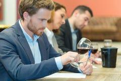 Spécialiste expert en vin goûtant le vin en verre photos stock
