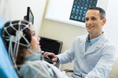 Spécialiste médical enregistrant les vagues electroencephalographic du cerveau de patients Image stock