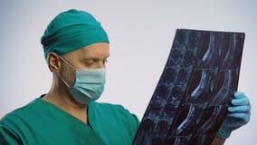 Spécialiste professionnel en épine regardant le balayage d'IRM, vérifiant le progrès de récupération banque de vidéos