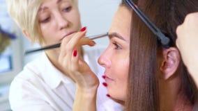 Spécialistes en salon de beauté faisant le maquillage et la coiffure professionnels pour la jeune femme de brune banque de vidéos