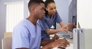 Spécialistes médicaux en afro-américain travaillant ensemble sur l'ordinateur Photographie stock