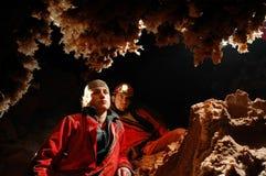 Spéléologues admirant des stalactites dans une caverne Photographie stock libre de droits