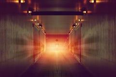 Spökelilla flickan syns på den mörka ingångsvägen med litet ljus Arkivbilder