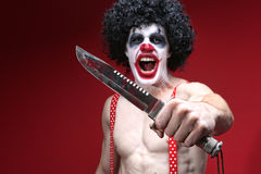 Spöklik clown Holding en blodig kniv Arkivfoto