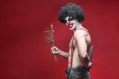 Spöklik clown Portrait på röd bakgrund Royaltyfri Foto