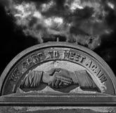 Spöklik gammal kyrkogårdgravsten mot stormig atmosfärisk himmel Arkivfoton