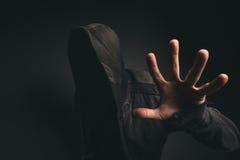Spöklik med huva person utan framsidan i mörkt rum arkivfoton