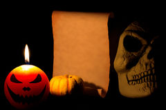 Spöklik stearinljus, liten pumpa, skalle och tomt papper Royaltyfri Foto