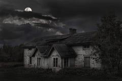 Spöklikt hus i Möksy Finland med den ljusa månen arkivfoton