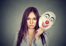 Spęczenie martwiąca się kobieta z smutnym wyrażeniem bierze daleko błazen maskę fotografia royalty free