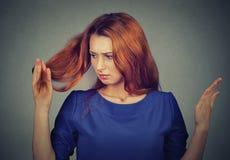 Spęczenie udaremniająca młoda kobieta zaskakiwał jej jest przegrywającym włosy, zauważać rozszczepione końcówki Zdjęcia Stock